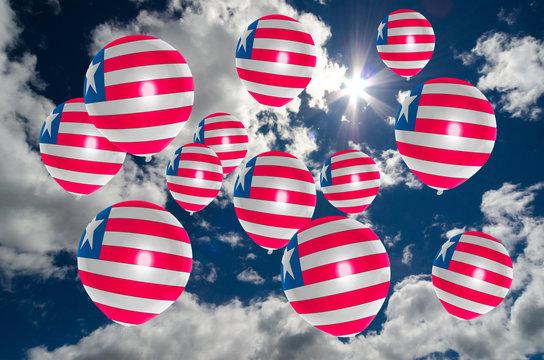 many balloons with liberia flag on sky