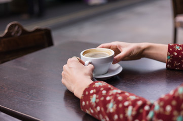 Hands of woman with cup of coffee outside