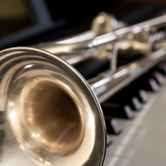 Trumpet segment closeup lying on piano keys