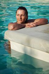 junge Frau entspannt im Pool und genießt die Sonne