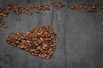 Coffee beans in the shape of a love heart on stone benchg.