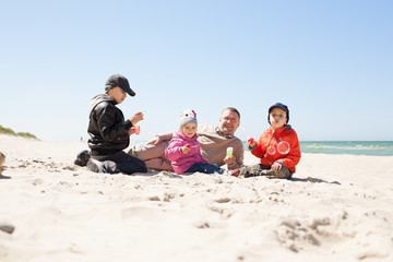 beach family lying on sand and play,  kids blowing bubbles