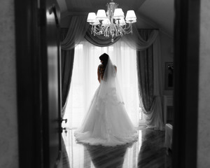 girl hair standing against a window in her wedding