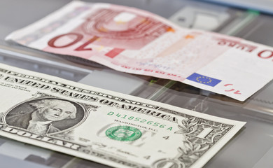 Denominations of one dollar and ten euros lie on scaner