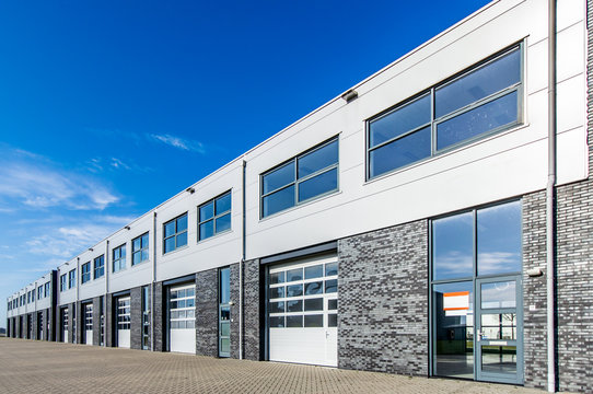 modern industrial building with loading doors and blue sky