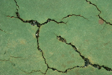 Close up view of a cracked tennis court surface