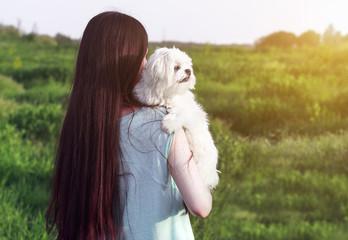 Beautiful girl with a young dog enjoying golden sunset
