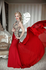 Attractive blond woman model wearing in elegant dress with blowi