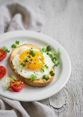 toast with egg on a white plate on a light surface