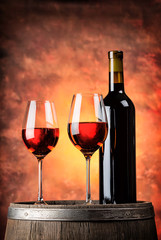 Bottle and two glasses of red wine on wooden barrel