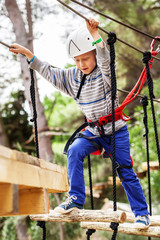 Boy on the rope track in safe equipment