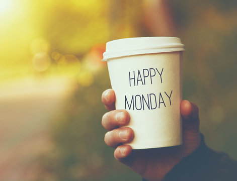 hand holding paper cup of coffee with Happy Monday motivational