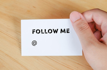 Follow me text on name card in hand
