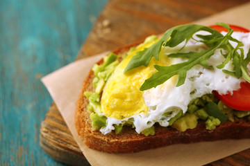 Tasty sandwich with egg, avocado and vegetables on cutting board, on color wooden background