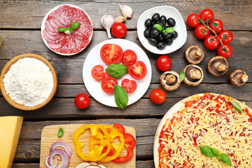 Food ingredients for pizza on table close up