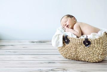Cute toddler sleeping in a wicker basket
