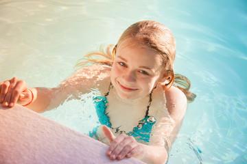 Beautiful teenage blond girl swims in pool
