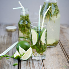 Lemonade with mint and lime on an old wooden table