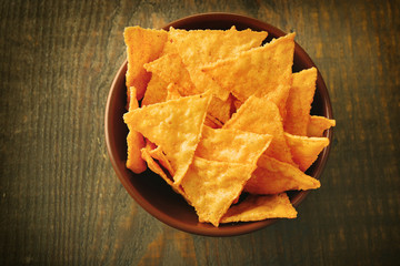Tasty nachos in color bowl, on wooden background