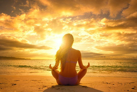 Young woman relaxing in lotus position during a beautiful sunset