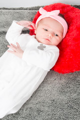 Newborn caucasian baby girl with pink bow