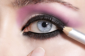 Close up on eyes , making colorful eyeshadows and eyeliner