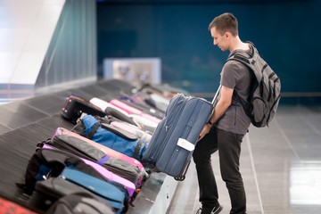 Young man collecting his luggage