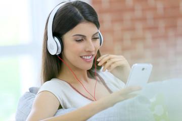 Smiling beautiful girl using smartphone and headphones
