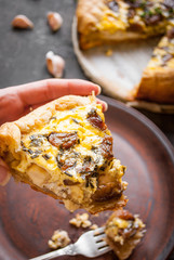 Woman's hand holding a caramelized garlic tart with goat cheese