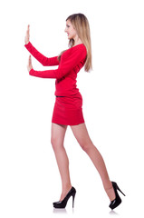 Young blonde girl in red short  dress pushing isolated on white