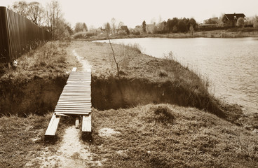 monochrome old photo of village pond and wooden bridge