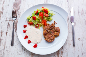 Grilled pork steak with salad on the plate