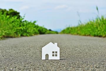 まっすぐな道路の上に置かれた白い家のシルエット