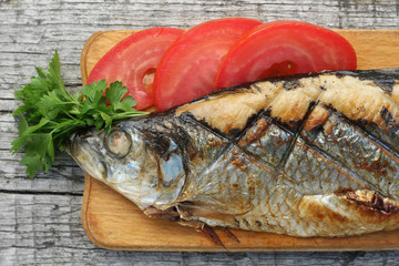 herring, grilled, sliced tomato and parsley on a cutting Boards