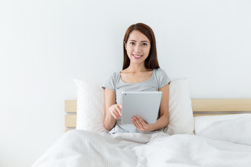 Woman sitting on bed and use of the digital tablet