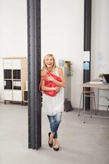 lachende frau im büro umarmt ihre rote tasche