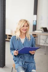 kreative unternehmerin sitzt mit einem block in ihrem büro
