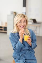 ältere frau im büro genießt einen smoothie