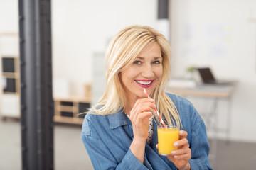 frau freut sich über einen frischen orangensaft