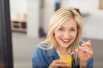 ältere frau freut sich über einen frischen orangensaft