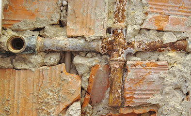 Broken water pipes on a broken brick wall