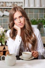 Sad woman drinking coffee