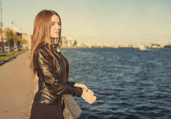 Pretty young woman student with long hair in leather jacket thinking near city river