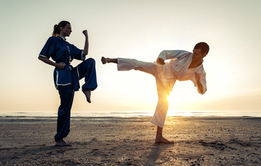 Aluminium Prints Martial arts couple training in martial arts on the beach
