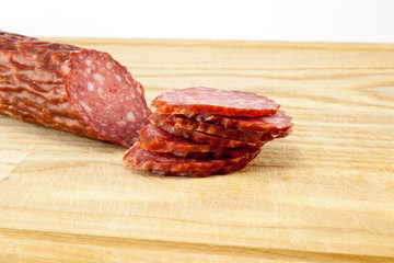 salami sausages on wooden board isolated