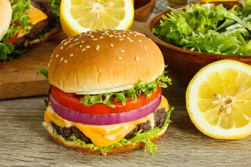 Homemade cheeseburger with fresh salad and lemon slices on wooden background