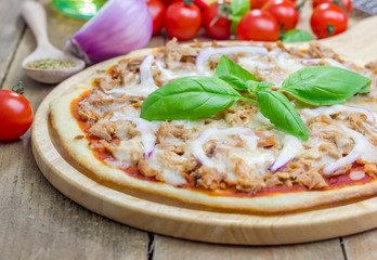 Pizza with tuna fish on a wooden board