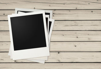 Polaroid photo frames on wooden background