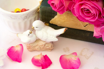 figurines wedding doves in love Valentine bouquet of pink roses on old books floral background is love tenderness vintage retro selective soft focus