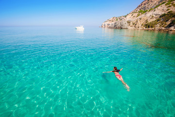 Woman swimming. Girl bathing in clear sea. Vacation on beach